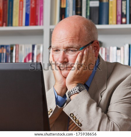 Elderly man sitting worried in front of his laptop in a library - stock photo