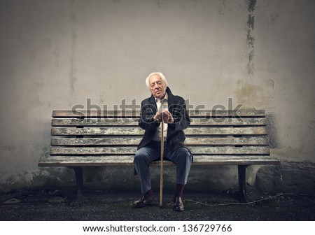 elderly man sleeps sitting on a bench - stock photo