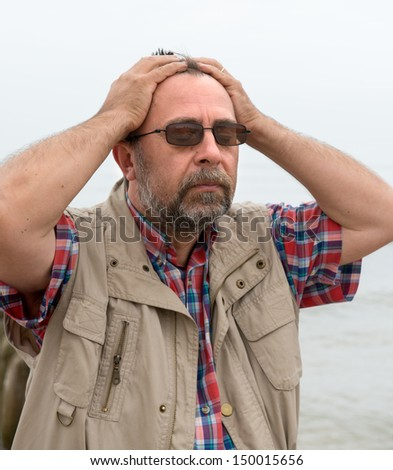 Elderly man suffering from headache on the sea background