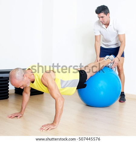 Elderly man suffering in the gym with personal coach