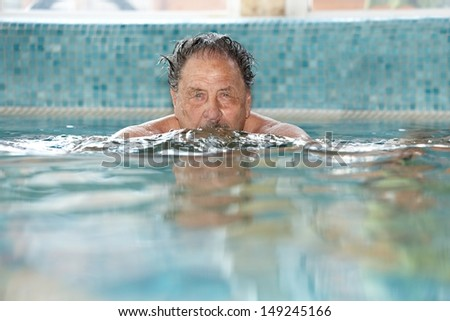 Elderly man swimming at swimming pool.