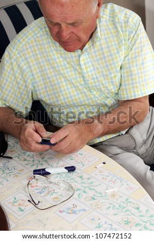 Elderly man testing his glucose level and reading the digital display on his portable glucometer to monitor his diabetes - stock photo