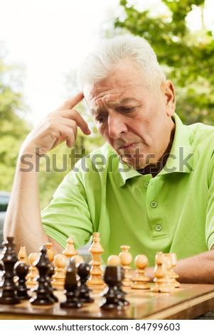 Elderly man thinking about next moves in chess. - stock photo