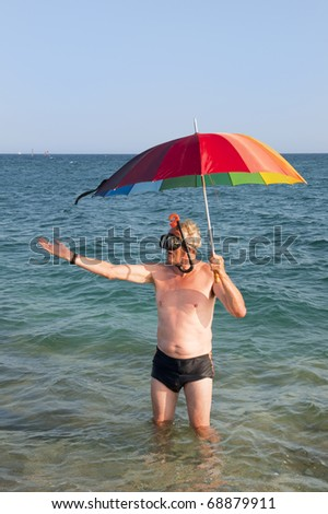 Elderly man under umbrella in the sea is testing if it's raining - stock photo