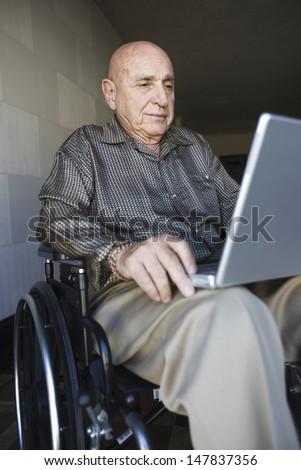 Elderly man using laptop in wheelchair - stock photo