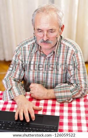Elderly man using laptop sitting at home. - stock photo