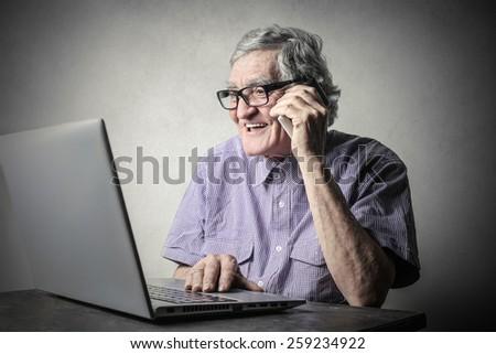 Elderly man using technology  - stock photo
