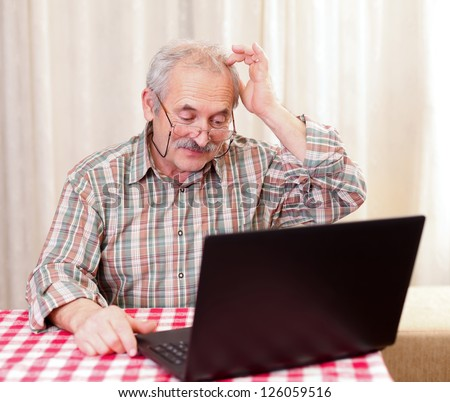 Elderly man using the laptop at home. - stock photo