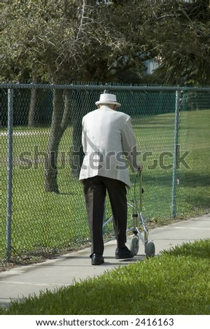 elderly man walking down a path holding onto a walker - stock photo