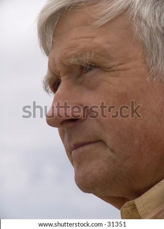 Elderly man watching and thinking - stock photo