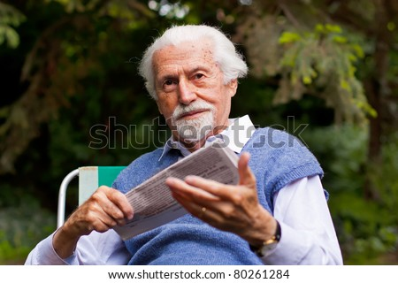 Elderly man with a newspaper in his hands, sitting on a chair outdoors. - stock photo