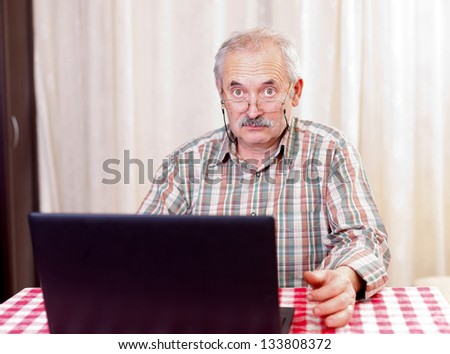 Elderly man with glasses using laptop at home. - stock photo