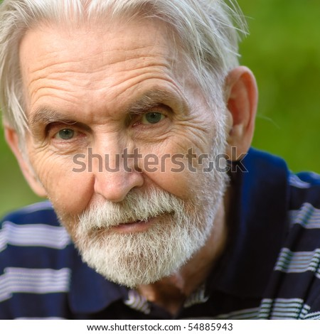 Elderly man with grey-haired beard close up against personal plot. - stock photo