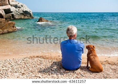 Elderly man with his dog at the summer beach - stock photo