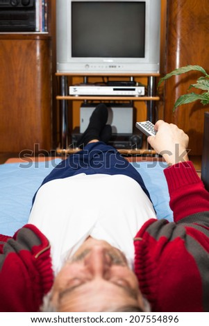 Elderly man with remote control watching TV at home. Shallow depth of field with focus on remote control. - stock photo