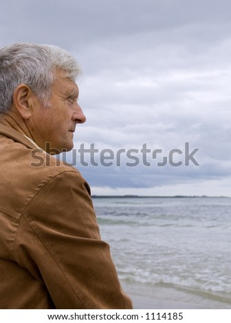 Elderly man with serious expression looking out over the ocean - stock photo