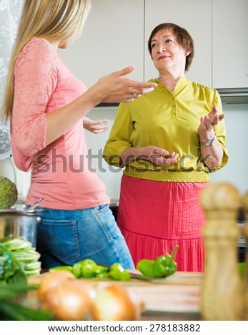 Elderly mother and adult daughter having serious conversation at kitchen