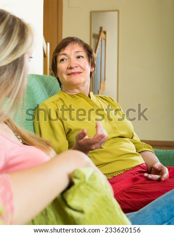 Elderly mother with daughter sitting on sofa and having serious conversation  - stock photo