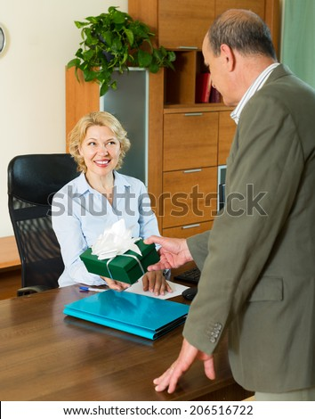 Elderly office manager congratulating happy female secretary on Women's Day