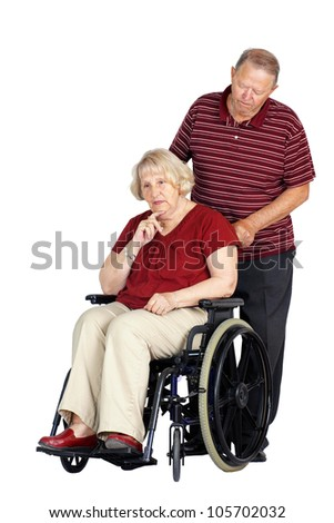 Elderly or senior couple with man caring for his wife in a wheelchair, looking sad or depressed, studio shot isolated over white background.