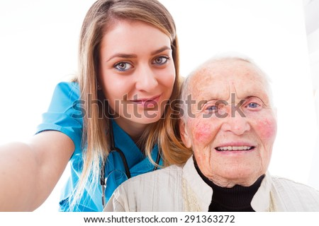 Elderly patient and young doctor sending confirmation to home about the good condition of the healing senior woman with the help of a selfie. - stock photo