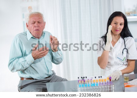 Elderly patient coughs into the doctor's office - stock photo