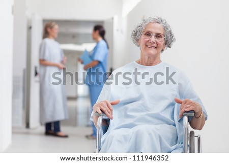 Elderly patient in corridor in hospital ward - stock photo