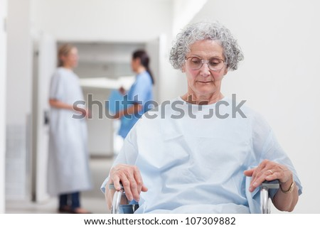 Elderly patient sitting in a wheelchair in hospital ward - stock photo