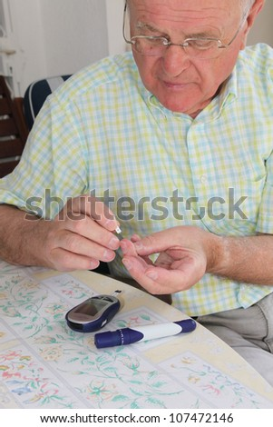 Elderly pensioner wearing glasses taking a small blood sample from his fingertip for use on his glucometer - stock photo