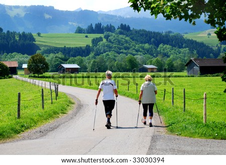 elderly people nordic walking in the bavarian alps germany - stock photo