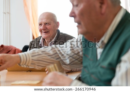 Elderly people playing rummy together - stock photo