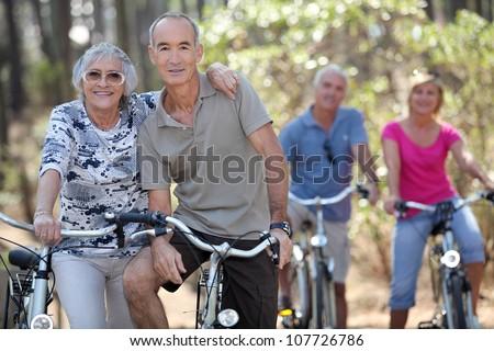 Elderly people riding their bikes - stock photo