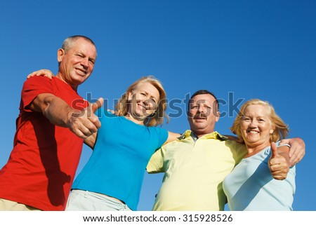 Elderly people showing thumbs up.