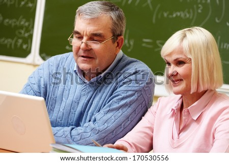 Elderly people using modern technologies for studying - stock photo