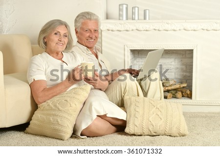Elderly people with tea and laptop