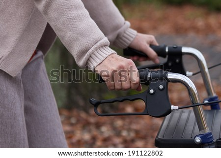 Elderly person during walking with walker, horizontal - stock photo