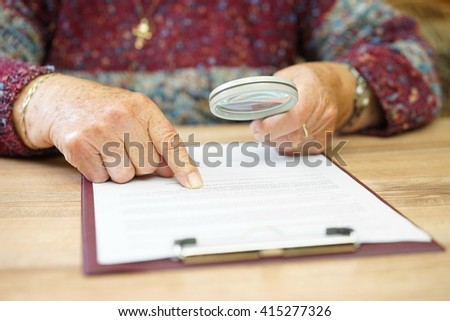 elderly person with magnifying glass checking document - stock photo