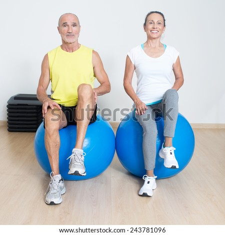 Elderly persons at physiotherapy lifting knees - stock photo