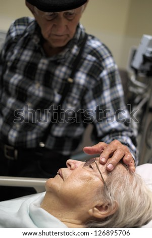 Elderly 80 plus year old woman in a hospital bed with her caring husband. - stock photo