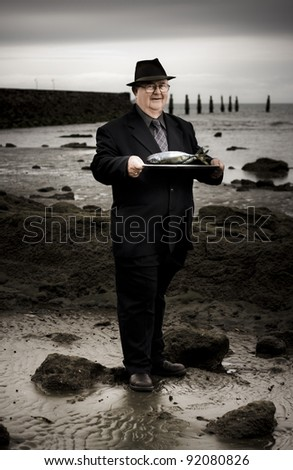 Elderly Restaurant Waiter Holding A Silver Platter Of Fish When Serving Up A Fishermans Seafood Platter On A Rocky Beach Sea Shore - stock photo