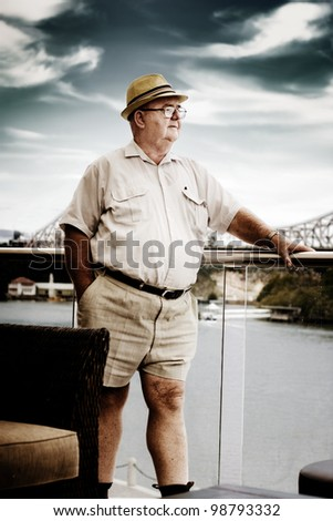 Elderly Retired Man In Shorts Standing On The Deck Of His Luxury Waterfront House Overlooking The Sea In A Financial Planning For A Wealthy Retirement Concept - stock photo