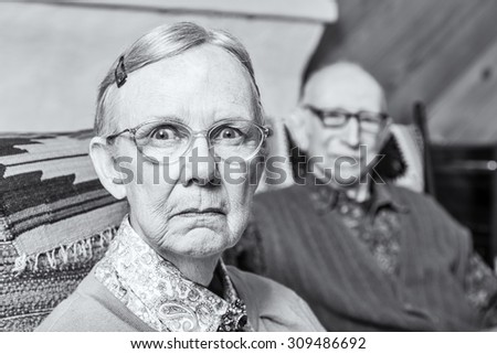 Elderly scowling couple seated in indoors woman - stock photo