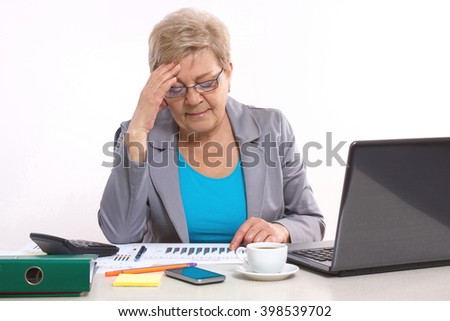 Elderly senior business woman holding hand on her head and working at desk in office, analyzing financial charts, business concept, analysis of sales plan, business report - stock photo