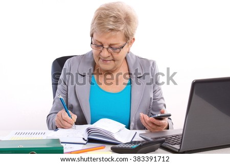Elderly senior business woman writing in notebook, using mobile phone and working at her desk in office, business concept, analysis of sales plan, business report - stock photo