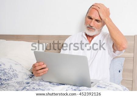 Elderly senior man checking for doctor on internet - stock photo
