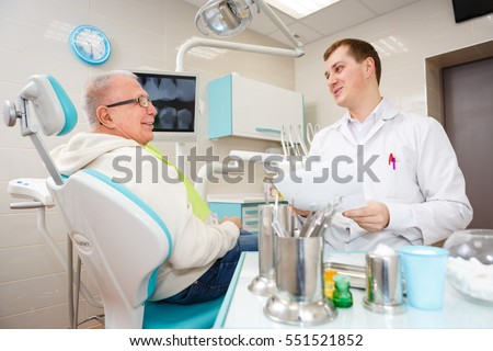 Elderly senior man on a review of a dentist, sitting in a chair