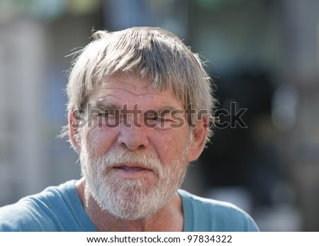 Elderly senior man with beard outdoors during the day - stock photo