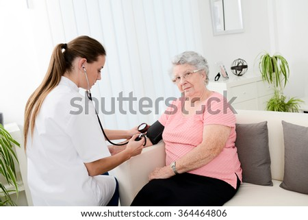 elderly senior woman with a young doctor having medical care at home