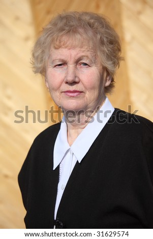 Elderly serious woman on wood background