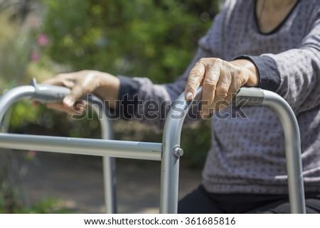 Elderly sitting in backyard with walker. - stock photo